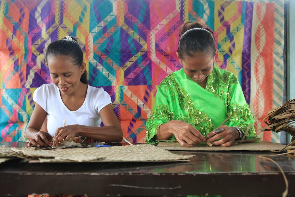 Women of the Bunawan Mat Weavers' Association work with their hands using Romblon material to produce handicraft items.
