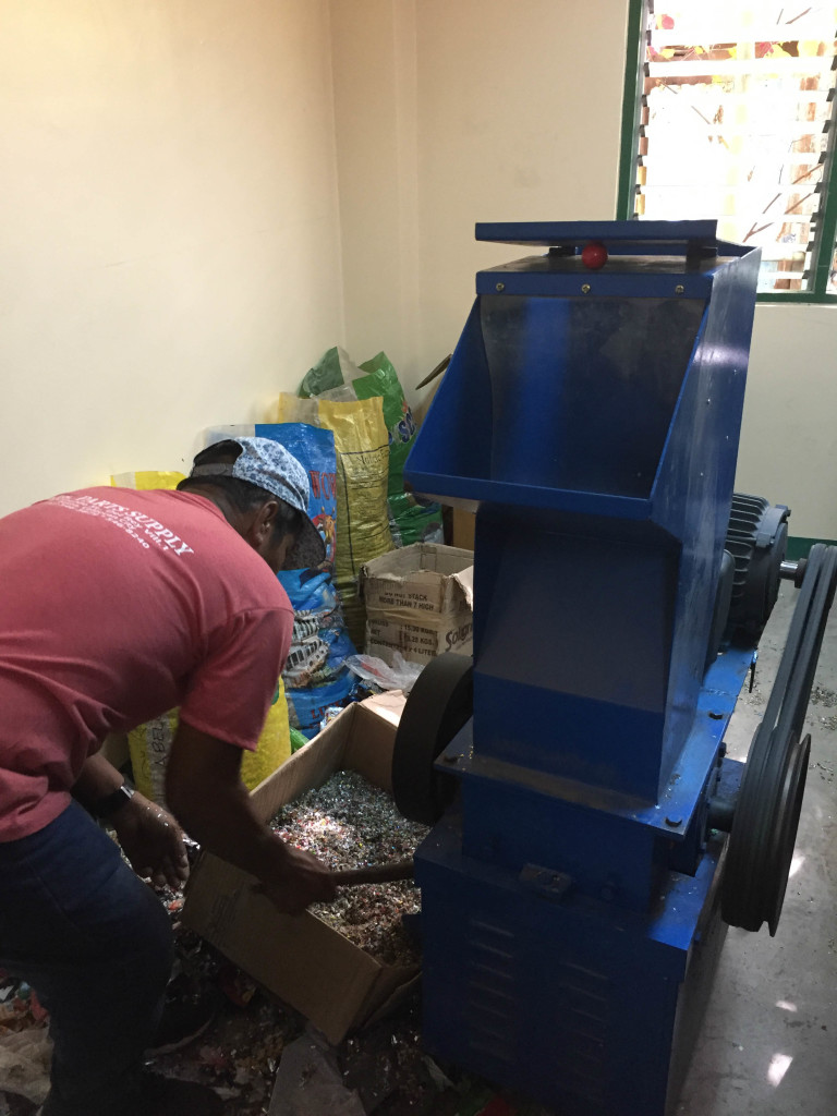 The school's machine technician demonstrates how to use the plastic shredder.