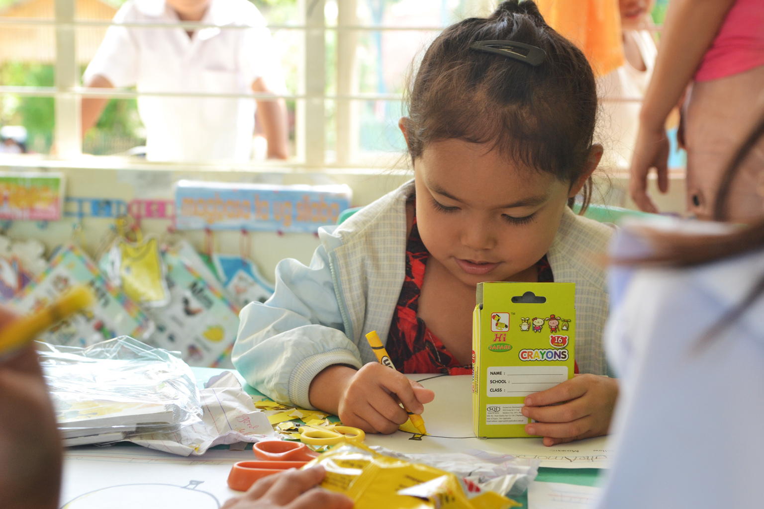 ADDING COLOR. A kindergarten pupil immediately used one of the crayons she received along with notebooks, paper and pencils inside the Silid Pangarap, a classroom for kindergarteners donated by Hedcor in partnership with Aboitiz Foundation.