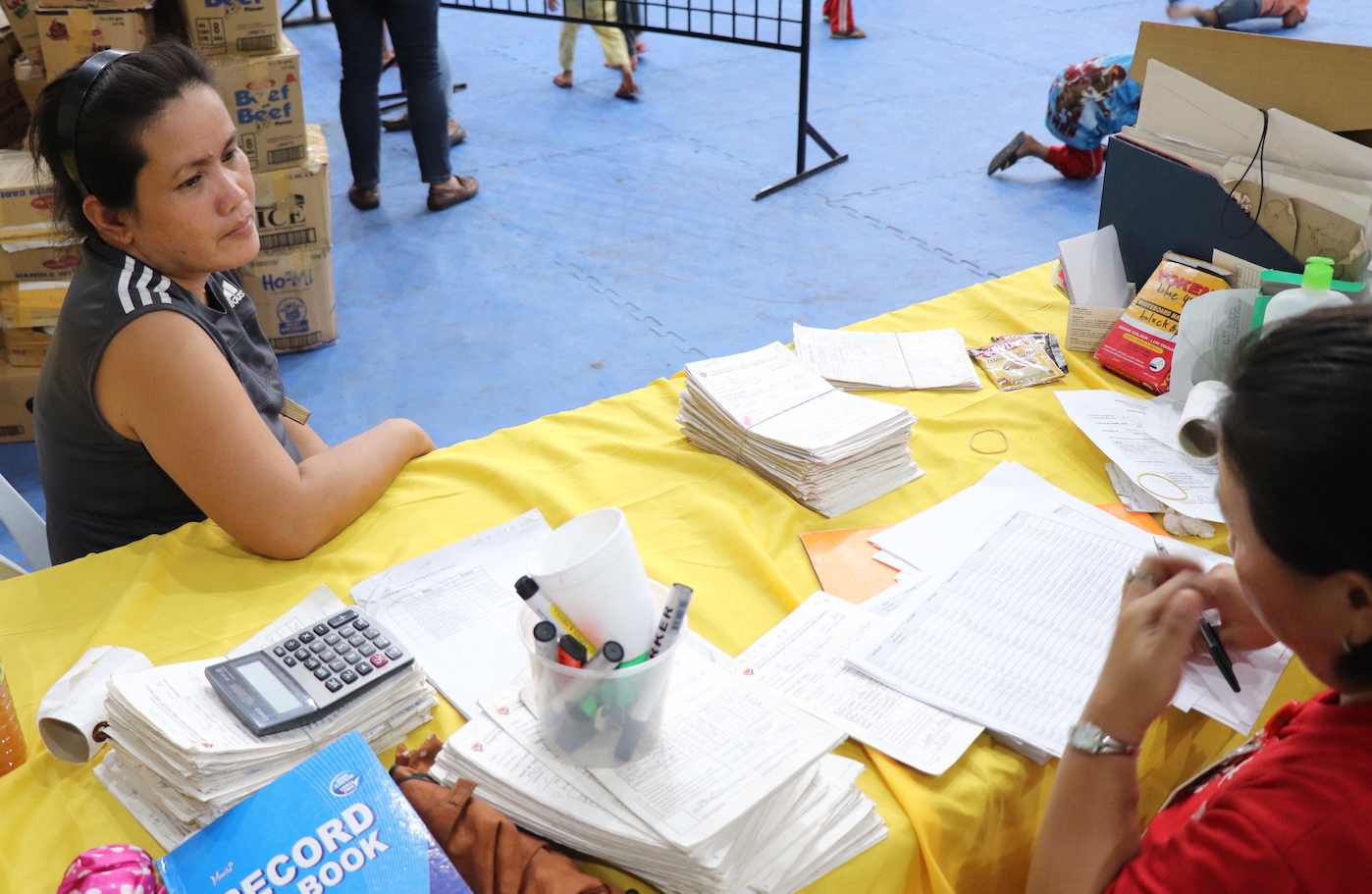 Flordeliza Lapitan (left), a 43-year-old mother of two, consults with a health worker at the Enan Chiong Activity Center regarding her son Jack's stomachache. The Lapitans are among hundreds of families in Naga City displaced by the massive landslide that struck Barangays Naalad and Tinaan on September 20.