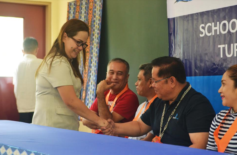 PARTNERS IN DEVELOPMENT. Mt. Apo National High School Teacher-In-Charge Marites Chan shakes hands with Hedcor's Vice President for Operations Rolando Pacquiao during the turnover ceremony of the two classrooms made possible by the partnership between Hedcor, the community, and the local government unit of Davao City.