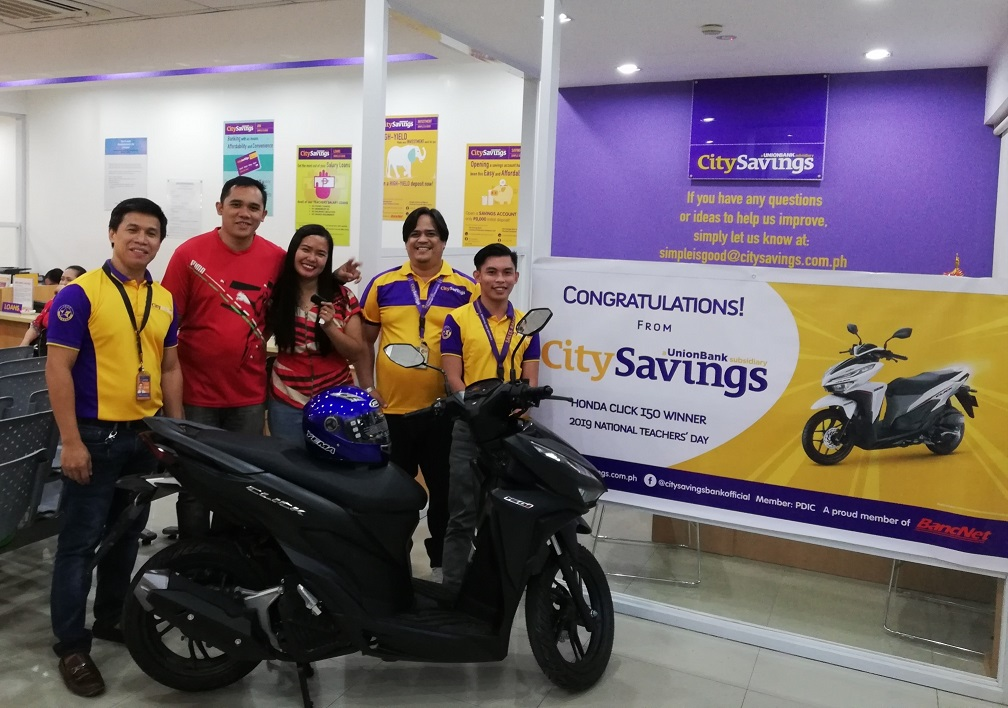 TEACHER TREATS: The winner of the brand new Honda Click Motorcycle happily receives her prize - Charmyne Tumala of Tangub City Central School