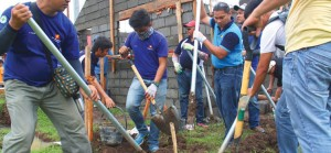 THE BAYANIHAN LINE. Davao Light and Power Co. employees share the fun in being a helping hand to each other by passing the hollow blocks to be used in building one of the Gawad Kalinga houses.