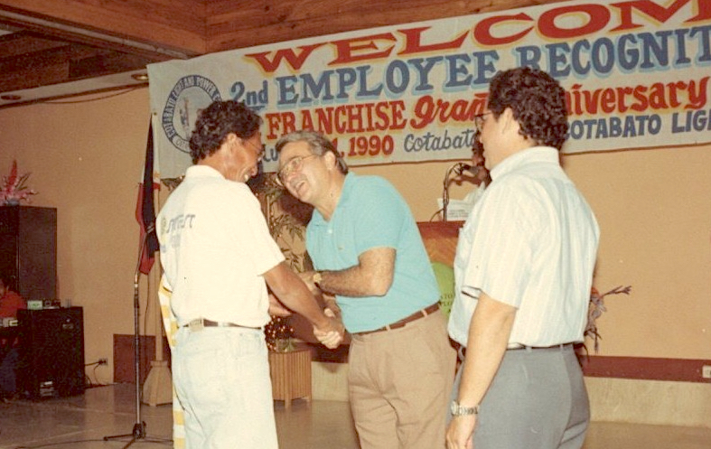 JRA, with EIA looking on, congratulating one of the team members of Cotabato Light at the company's Recognition Day, August 1990.