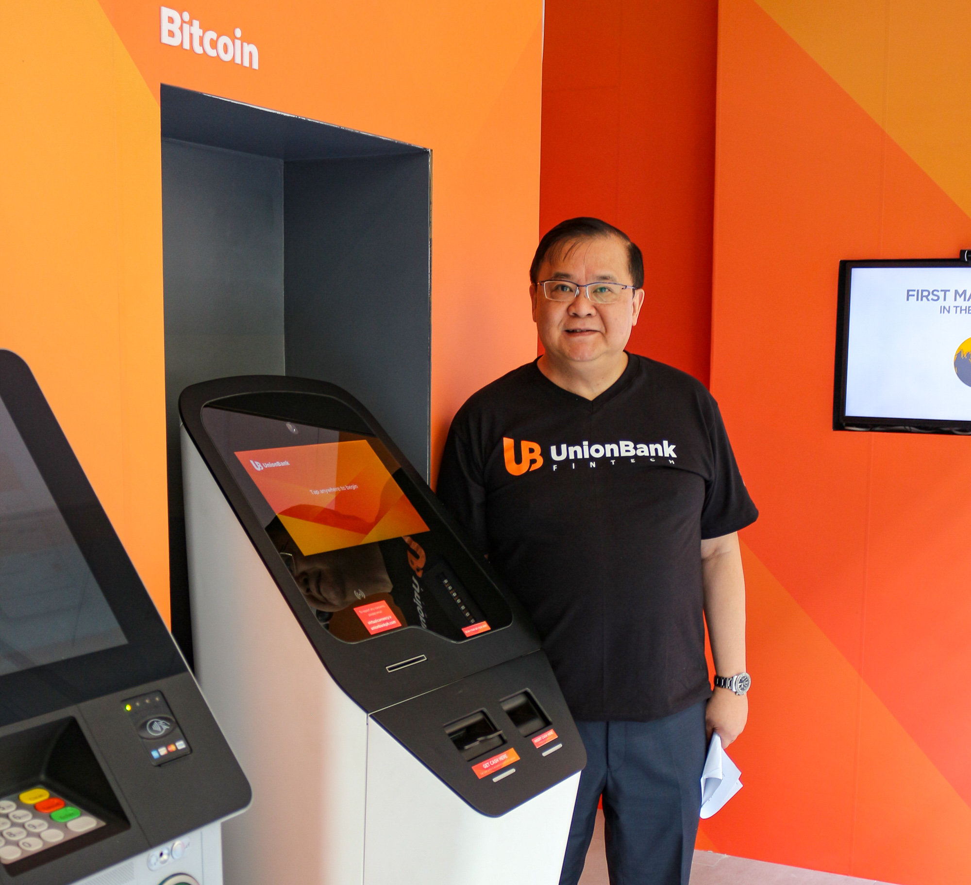 UnionBank President Edwin Bautista next to the country's first bi-directional cryptocurrency ATM, which allows both purchase and sale of Bitcoins.